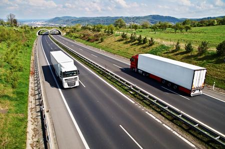 Gang weg met de overgang voor dieren, naar beneden de snelweg twee vrachtwagens, op de achtergrond de bergen stad en bosrijke, bekijken van boven