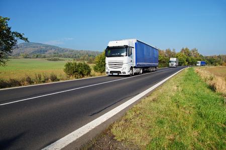 田園地帯、フィールド、背景の樹木が茂った山の道の 3 つの白いトラック 写真素材