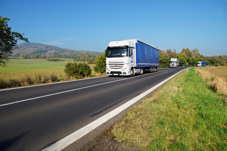 Three white trucks on the road in the countryside, fields and wooded mountain in the background Standard-Bild