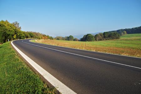 田舎道のベンド、バック グラウンドでフィールド、地平線上の森の空アスファルト道路