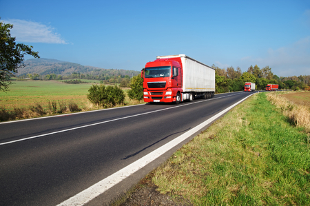 Three red trucks on the road in the countryside, fields and wooded mountain in the background Standard-Bild