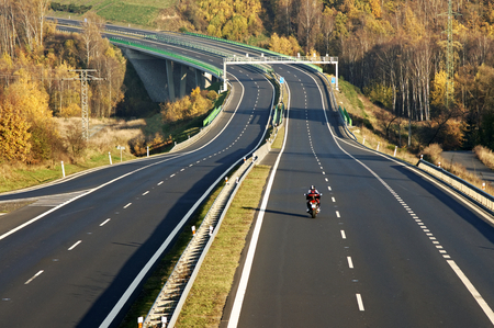 電子通行料のゲート、紅葉の落葉広葉樹林、バイクに乗ってフォア グラウンドで渓谷の橋を渡って高速道路リードを空、上からの眺め