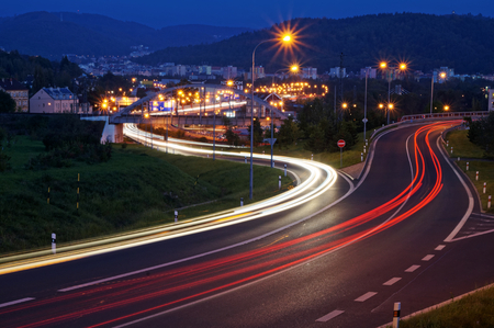 The city with street lighting in the valley at night, the light path headlights of cars, wooded mountains in the background, view from above Standard-Bild