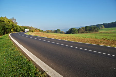 Asphalt road in the countryside, white truck coming around in the distance the bend, forest on the horizon Banco de Imagens