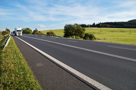 Asphalt road in a rural landscape. The arriving white truck on the road. Meadow and forest in the background.