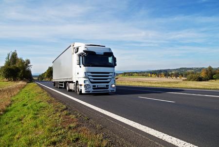 Fehér teherautó közlekedik az aszfaltút a vidéken. Mezők, rétek és fák kora őszi színek a háttérben.