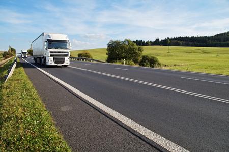 Aszfalt út egy vidéki táj. Az érkező két fehér kamion az úton. Rét és erdő a háttérben.