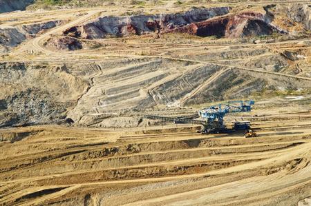 mining: La mina de pared de la superficie con los minerales de colores expuestos, el equipo de la minería a cielo en el fondo, vista desde arriba, vista superior Foto de archivo