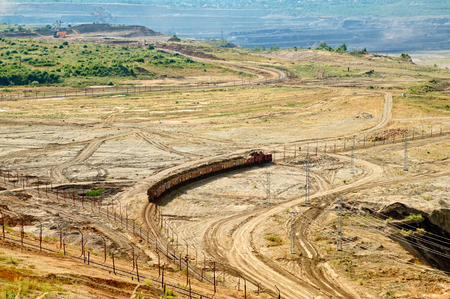 forefront: View of the open-pit mine, mining train carrying excavated materials at the forefront, mining machines in the background in the distance, view from above