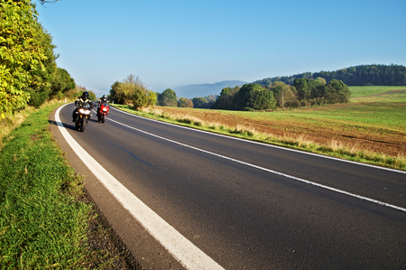 Country landscape with an asphalt road. Two motorcycles on the road. Field, forest and forested mountains in the background.