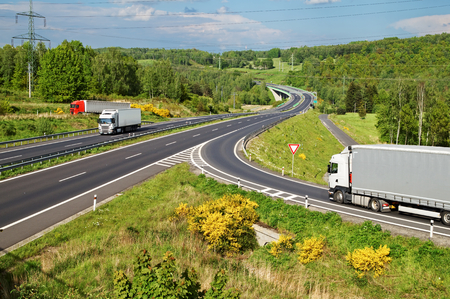 Highway in the countryside. Three moving trucks. Electronic toll gate and a bridge in the distance. View from above.