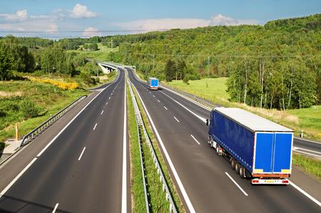 시골에서 고속도로 아래로 운전하는 파란색 트럭. 전자 톨게이트와 멀리있는 다리. 위에서 볼.