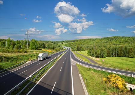 숲 사이 아스팔트 공도에 접근 도로. 도로에 흰색 트럭입니다.