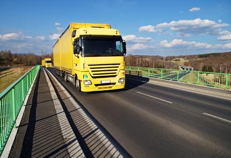 transport truck: Two yellow trucks driving across the bridge over the motorway.