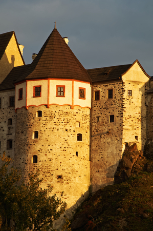 historical periods: Detail of the Gothic-Romanesque castle Loket in the Czech Republic. Warm sunlight of late afternoon. Dark cloudy sky in the background.
