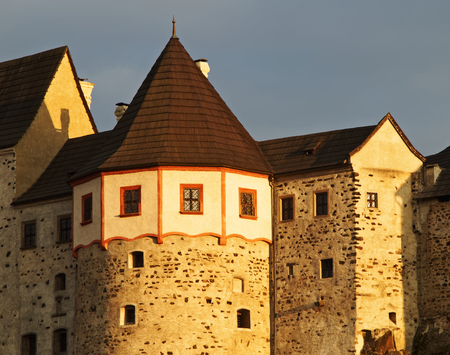 listed buildings: Detail of the Gothic-Romanesque castle Loket in the Czech Republic. Warm sunlight of late afternoon. Dark cloudy sky in the background.