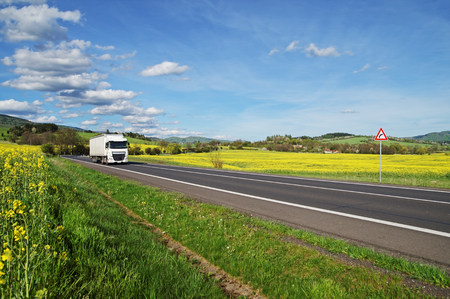 White truck driving on the asphalt road between yellow flowering rapeseed field in the rural landscape. Wooded mountains in the background. Blue sky with white clouds. Standard-Bild