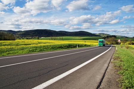 緑色のトラックは、農村風景の黄色開花菜の花フィールドの間アスファルト道路の距離から到着します。緑豊かな山を背景に。白い雲と青い空。 写真素材