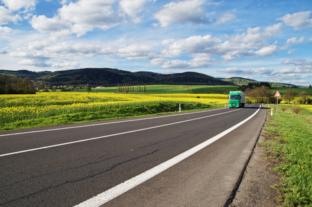 Green truck arrives from a distance on an asphalt road between the yellow flowering rapeseed field in the rural landscape. Wooded mountains in the background. Blue sky with white clouds.