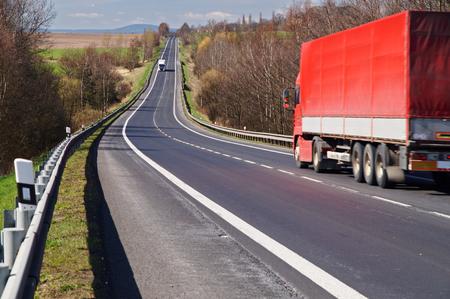 Il camion rosso percorrendo una strada asfaltata in campagna in primavera. Camion bianco arriva da lontano.