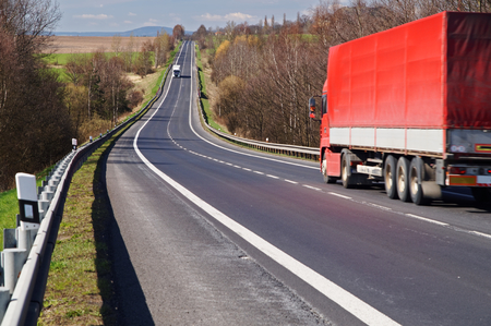 green road: The red truck driving along an asphalt road in the countryside in early spring. White truck arrives from a distance.