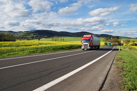 Red and green trucks arrives on an asphalt road between the yellow flowering rapeseed field in the rural landscape. Wooded mountains in the background. Blue sky with white clouds.