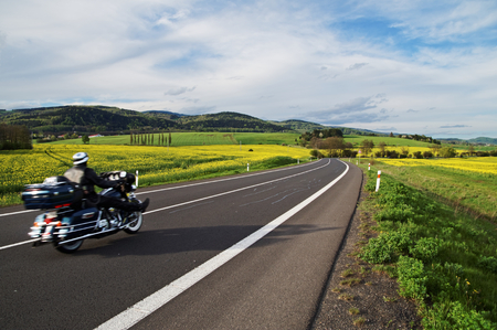 motorcycle road: Motorcycle traveling along an empty asphalt road between yellow blooming rape fields in the rural landscape. In the background of forested mountains. Stock Photo