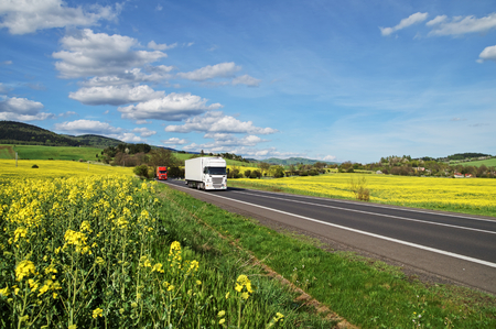 Trucks driving along the asphalt road between rapeseed fields. Wooded mountains in the background. Blue sky with white clouds. Stock Photo