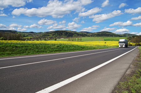 haulage: White truck arrives from a distance on an asphalt road between the yellow flowering rapeseed field in countryside. Wooded mountains in the background. Blue sky with white clouds.