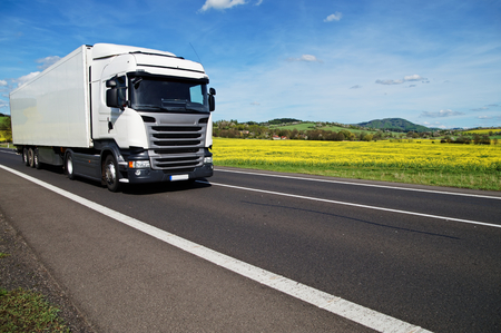 haulage: White truck on the asphalt road between yellow flowering rapeseed field in a rural landscape. Villages and forested mountains in the background. Blue sky with white clouds. Stock Photo