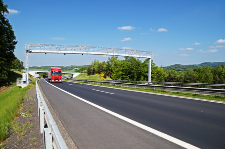 toll: Red truck arriving toward electronic toll gate over a highway in a wooded landscape. Bridge and forested mountains in the background. White clouds in the blue sky.