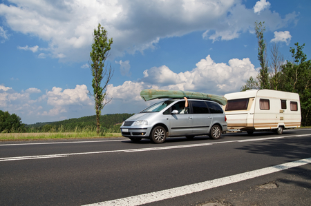 Car with a canoe on the roof and caravan traveling on an asphalt road in a rural landscape. Traveling on vacation. Summer day with blue skies and white clouds.