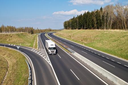 ciężarówka: Pusta droga ekspresowa asfaltowa z jazdy białego ciężarówka na wsi. Wejście do drogi ekspresowej. Widok z góry. Wyczyść słoneczny dzień z niebieskim niebem i białymi obłokami.