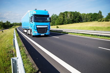 Blue truck on asphalt expressway in the countryside. Sunny day.