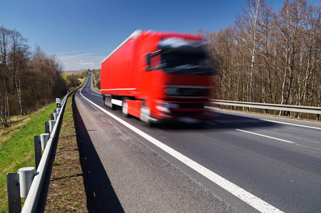 Speeding motion blur red truck on asphalt road in a rural landscape. Sunny day with blue skies. Standard-Bild