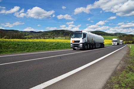 화이트 유조선 및 트럭 시골에서 노란색 꽃 유채 필드 주위 아스팔트 도로 따라 운전. 백그라운드에서 숲이 우거진 된 산입니다. 푸른 하늘에 흰 구름