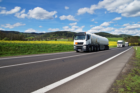 White tanker and trucks driving along the asphalt road around the yellow flowering rapeseed field in countryside. Wooded mountains in the background. Blue sky with white clouds.