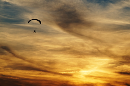 high flier: Paragliding in clouds at sunset. Silhouette against a background a cloudy sky colors the sunset.