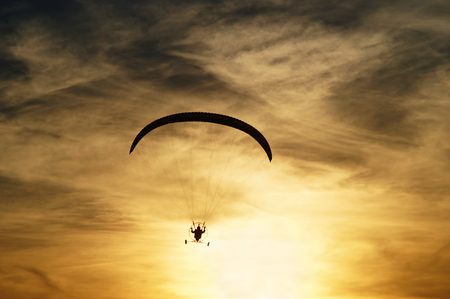 high flier: Paragliding at sunset. Silhouette against a background a cloudy sky colors the sunset.