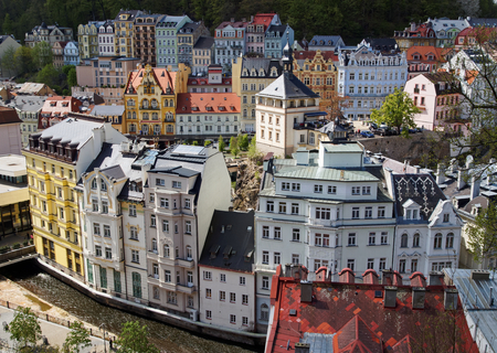 View of the historic town in the wooded valley. Town of Karlovy Vary in the Czech Republic. Old houses with colorful facade. View from above.