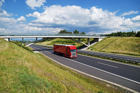 Red truck on highway goes under the concrete bridge in the countryside. View from above. Sunny day with blue sky and white clouds. Stock Photo