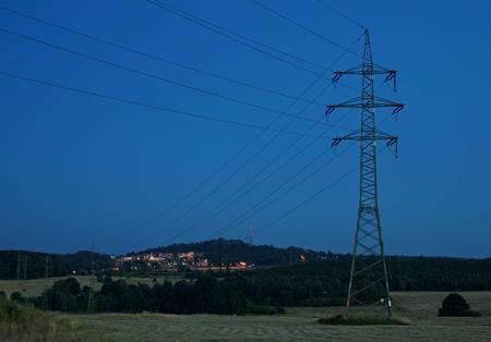 高電力線鉄塔は、バック グラウンドで電気照明都市するものです。夕方には農村風景。