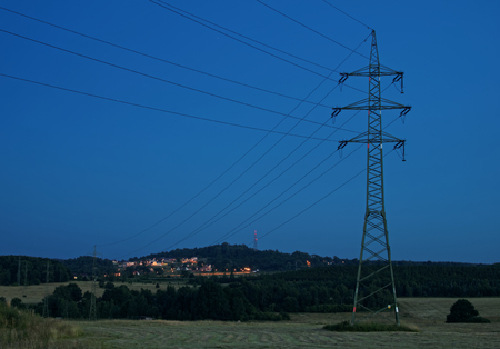 High power line pylons are intended to electrically lighted city in the background. Rural landscape in the evening. Banco de Imagens