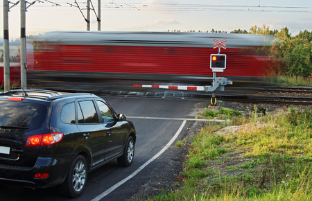Speeding motion blur red train passing through a railway crossing with gates. Black car standing in front of the railway barriers on an asphalt road.