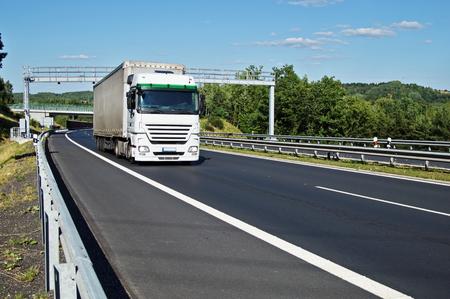白いトラックの緑豊かな風景の中のアスファルトの道路に電子通行料のゲートを通過します。橋と森林に覆われた山を背景に。青い空に白い雲。