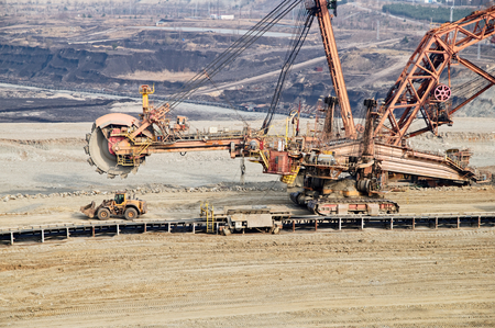 Giant mining excavator on the bottom surface mine. Brown coal deposits in the background. View from above.