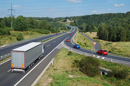 Asphalt highway with white truck and red passenger cars in wooded country. Electronic toll gate in the distance. View from above. Sunny summer day with blue skies. Standard-Bild