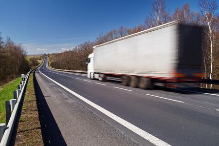 과속 모션 과속 농촌 풍경에 빈 아스팔트 도로에 흰색 트럭. 푸른 하늘이 맑은 날.