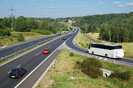 White Bus arriving to the asphalt highway on the slip road in a wooded landscape. Red passenger cars and truck driving on the highway. Electronic toll gate in the distance. View from above. Sunny summer day with blue skies.