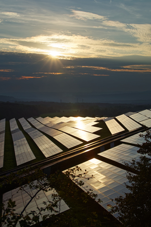 Solar power plant at sunset amongst forests. The smoking smokestack and forested mountains fading into the misty haze and smog in the background. Stock Photo